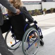 Female executive being pushed in wheelchair — Stock Photo