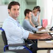 Employee in wheelchair with laptop — Stock Photo