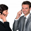 Two businesspeople making simultaneous calls — Stock Photo