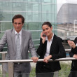 Stock Photo: Businessmen and women on phone outside.