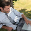 Young executive working in the park — Stock Photo