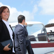 Stock Photo: Businesspeople next to airplane