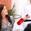 Waitress presenting bottle of wine to couple - Stock Photo