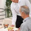 Young waiter serving ham salad — Stock Photo