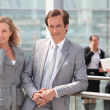 Male and female executives outside conference center — Stock Photo #7706196
