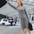 Businesswoman stopping taxi — Stock Photo