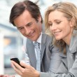 Businessman and woman with phone — Stock Photo