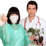 Medical team attaching a drip to a bonsai tree — Stock Photo