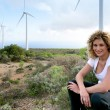 Young woman sitting near wind turbines — Stock Photo