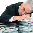 Man lying on paperwork - Stock Photo