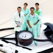 Portrait of medical staff amid giant clipboard and sphygmomanometer — Foto de stock #7708098
