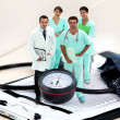 Foto de Stock  : Portrait of medical staff amid giant clipboard and sphygmomanometer