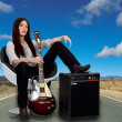 Stylized female guitarist with her amp on road — Stock Photo #7708143