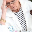 Senior woman taking drugs - Stock Photo