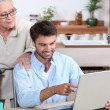 Man showing old lady how to use computer — Stock Photo