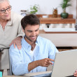 Man showing old lady how to use computer — Stock Photo #7708659