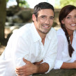 Couple in white leaning on a wooden fence — Stock Photo