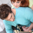 Young couple playing a guitar at home — Stock fotografie