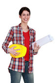 Craftswoman holding a helmet and a blueprint — Stock Photo