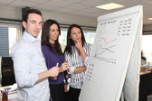 Sales team standing at a flipchart — Stock Photo