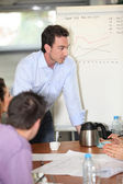 Sales manager giving explanations to group — Stock Photo