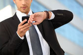 Young executive checking his watch against a cellphone — Stock Photo