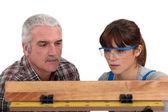 Carpenter and female apprentice — Stock Photo