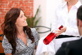 Waitress presenting bottle of wine to couple — Stock Photo
