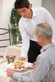 Young waiter serving ham salad — Stockfoto