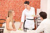 Casal interagindo com a empregada de mesa num jantar — Fotografia Stock