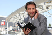 Businessman on phone with diary — Stock Photo