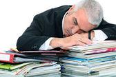 Man lying on paperwork — Stock Photo
