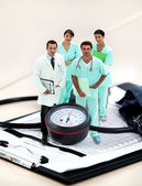 Portrait of medical staff amid giant clipboard and sphygmomanometer — Stock Photo
