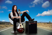 Stylized female guitarist with her amp on the road — Stock Photo