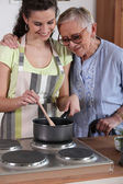 Granddaughter cooking for her grandmother — Stock Photo