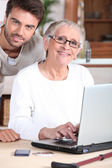 Young man helping senior woman with a laptop computer — Stock Photo