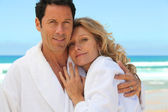 Mid aged couple wearing a bathrobe near the sea — Stock Photo