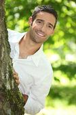 Peekaboo. Man in a white shirt peering round a tree. — Stock Photo