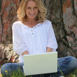 Stock Photo: Womon laptop under tree