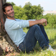 Man sitting against tree — Stock Photo