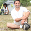 Royalty-Free Stock Photo: A man seated, behind him, a canvas tent and a woman