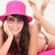 Young woman lying on the beach in bikini and a bright pink hat — Stock Photo