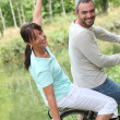 A couple doing bike in the country, the woman is doing airplane with her ar — Stock Photo