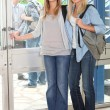 Female students opening door — Stockfoto