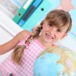Pupil standing behind a globe - Stock Photo