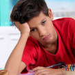 Bored little boy in classroom - Stock Photo