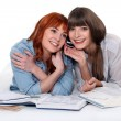 Two female students studying listening a mobile — Стоковое фото