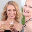 Two women with champagne flutes — Stock Photo