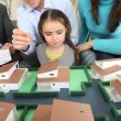 Young family looking at model housing — Stock Photo