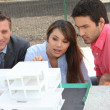Agent and young couple with a model of a new development — Stock Photo
